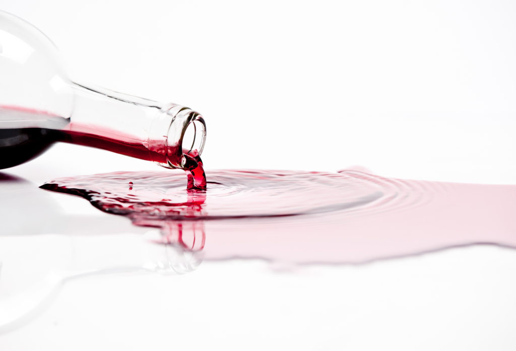 Spilled red wine on white background.
