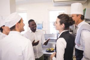 Kitchen staff wearing different uniforms.